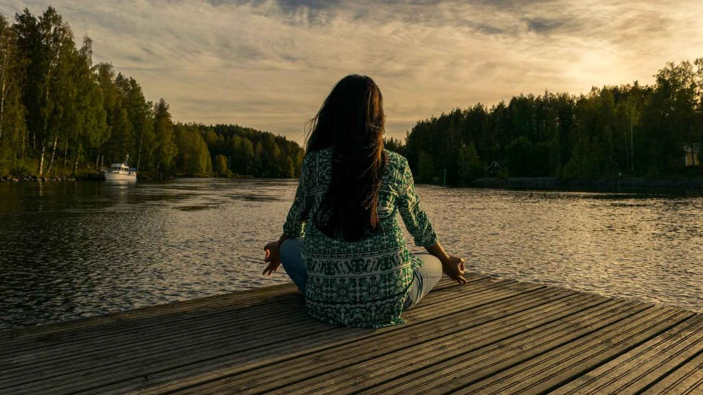 kvinne mediterer ved vann, mindfulness og meditasjon